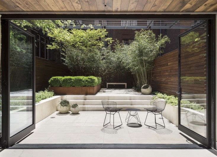 "In Manhattan, an airy hedge of bamboo provides screening at the garden's perimeter while a pared-down palette of green and white focuses the eye on the center of the space. ""The white limestone is like a canvas. When the sun is directly overhead, you can see the shadows of the bamboo and other plants starkly against it,"" says designer Julie Farris. Photograph by Matthew Williams."