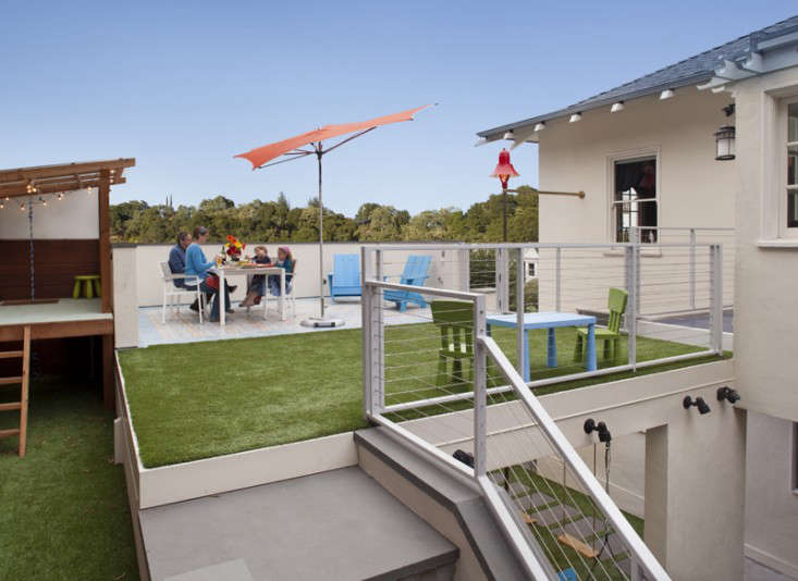 above the roof above the carport becomes an outdoor terrace carpeted with artificial turf a tucci razor shade umbrella from dwr offers protection from