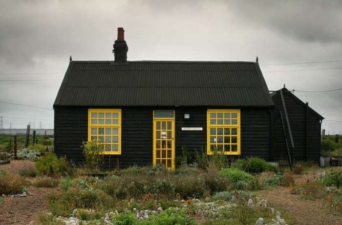 The facade of filmmaker Derek Jarman's black seaside cottage in Dungeness, Kent is lightened by sunshine yellow trim. Photograph by Howard Sooley, from Garden Visit: Derek Jarman's Prospect Cottage at Dungeness.