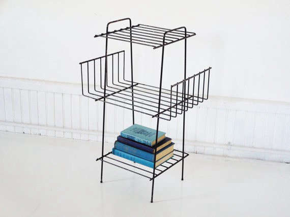 above a sturdy vintage mid century magazine rack has three wire shelves that can do double duty to display houseplants is 66 from the white pepper via
