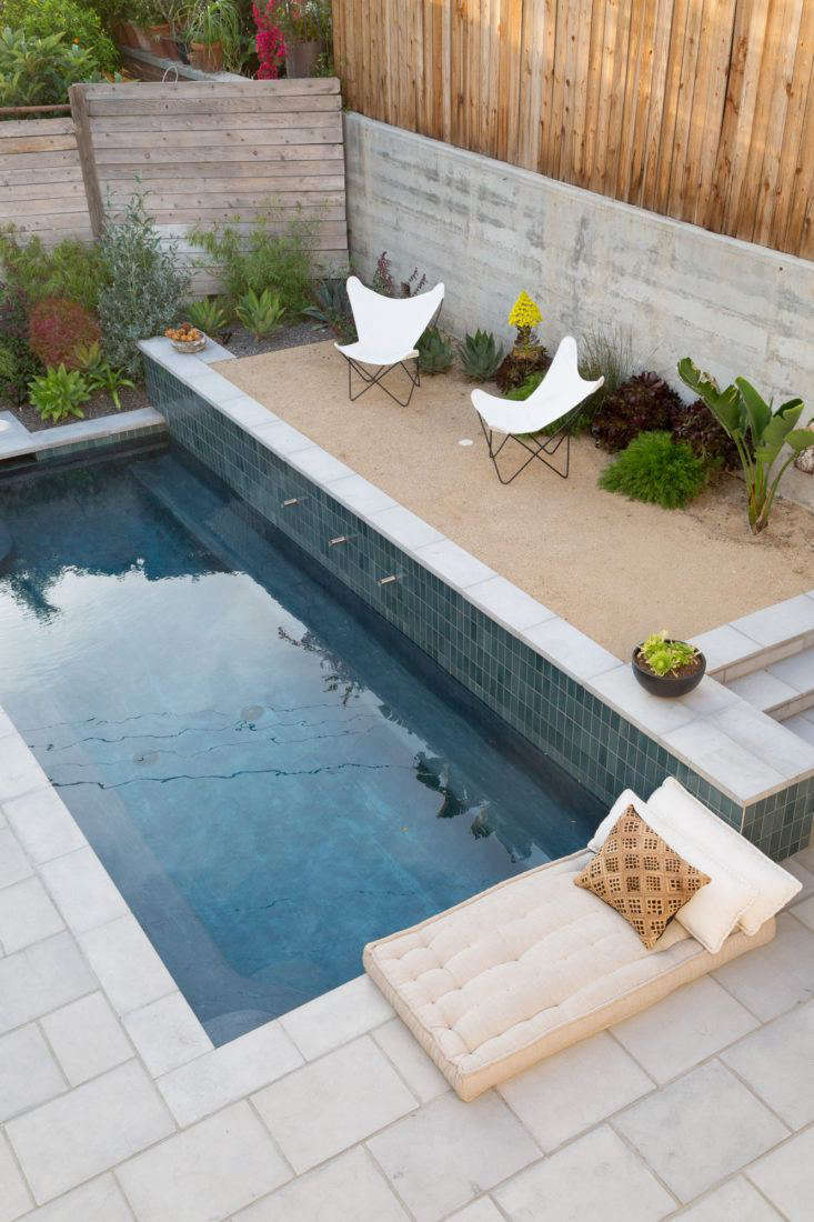 Next to the pool, a gravel courtyard is like a luxe mini beach in costume designer Gordana Golubovic's luxe, secluded LA backyard. Photograph by Lauren Moore.