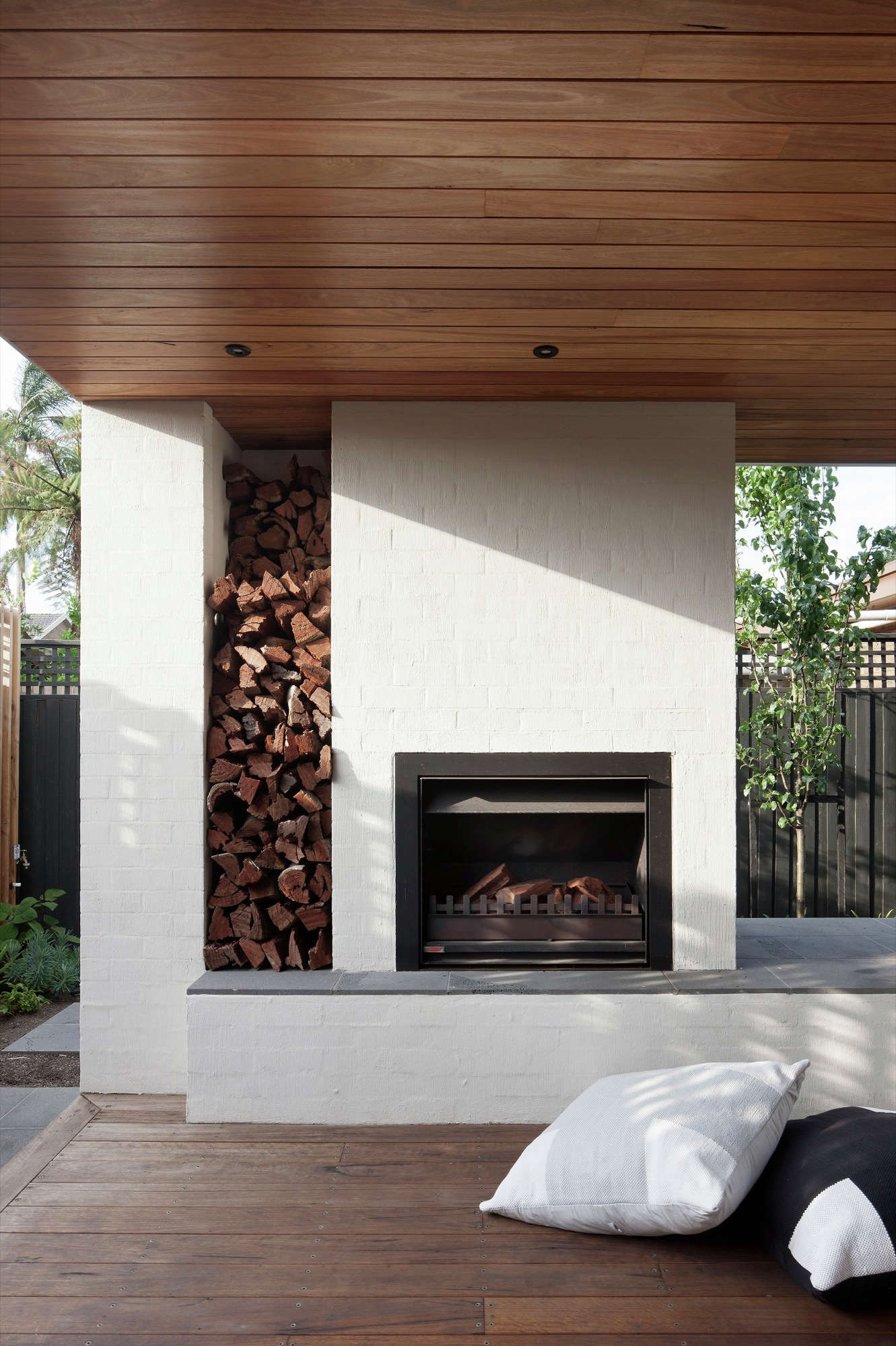 During a remodel to a 60s-era house in Melbourne suburb of Caulfield, Australia the homeowners added an open-air living room with a fireplace. Photograph by Shannon McGrath via Bower Architecture and Arch Daily.