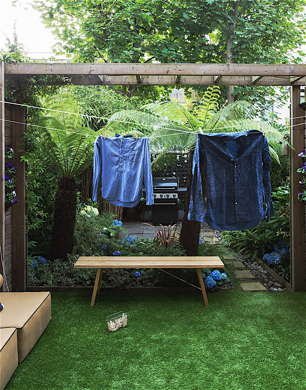 Christine Chang Hanway, London garden, Garden as exterior room, two blue shirts hanging on clothes line which attaches to garden shed, Matthew Williams | Gardenista