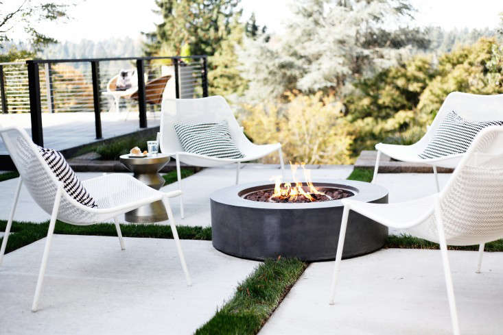 An Outdoor Lounge Area Has A Fire Pit As A Focal Point In A Garden In