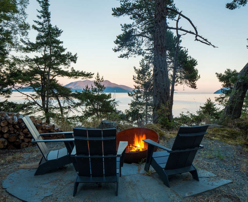 Loll's Adirondack chairs, made of recycled HDPE plastic (mostly single-use milk jugs discarded by consumers), are perfect for rainy climates and require little maintenance. Here they are around a backyard fire pit in the San Juan Islands of Washington state. Photograph by Sean Airhart courtesy of Heliotrope Architects, from Outdoor Furniture Spotlight: Colorful, Recycled Designs from Loll.