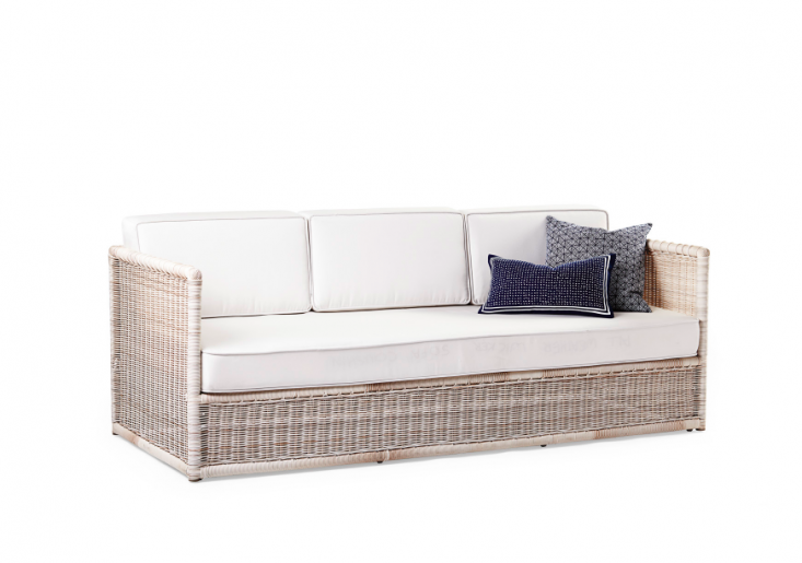 A Pacifica Sofa woven of all-weather resin on a powder-coated aluminum frame comes with cushions covered in all-weather Sunbrella fabric (cushions are available in white, shown, and in denim). It measures 83 inches long; $2,598.