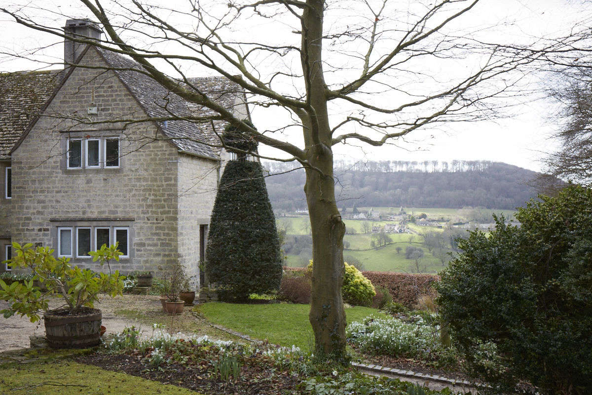 In the center of the garden sits the Cotswold stone house with views to the borrowed landscape of southerly hills leading the eye even further.