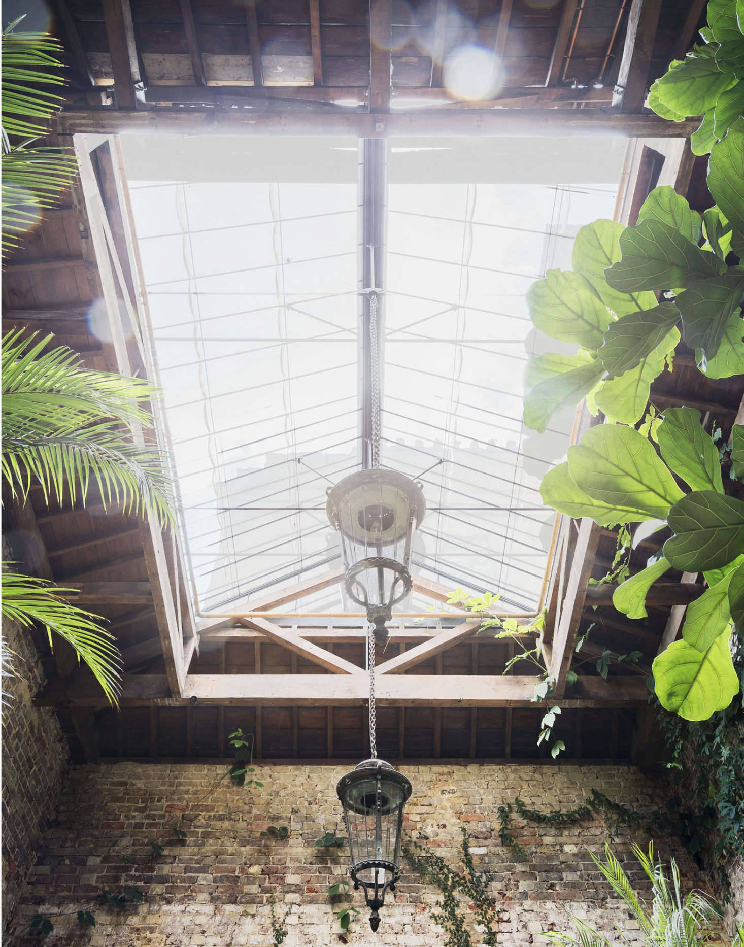 A th-century Venetian hanging lantern (one of a pair) is wired for electricity and hangs from a skylight Van Duysen designed to look like a throwback to a Victorian greenhouse. Exposed copper heating pipes glow in the light on sunny days.