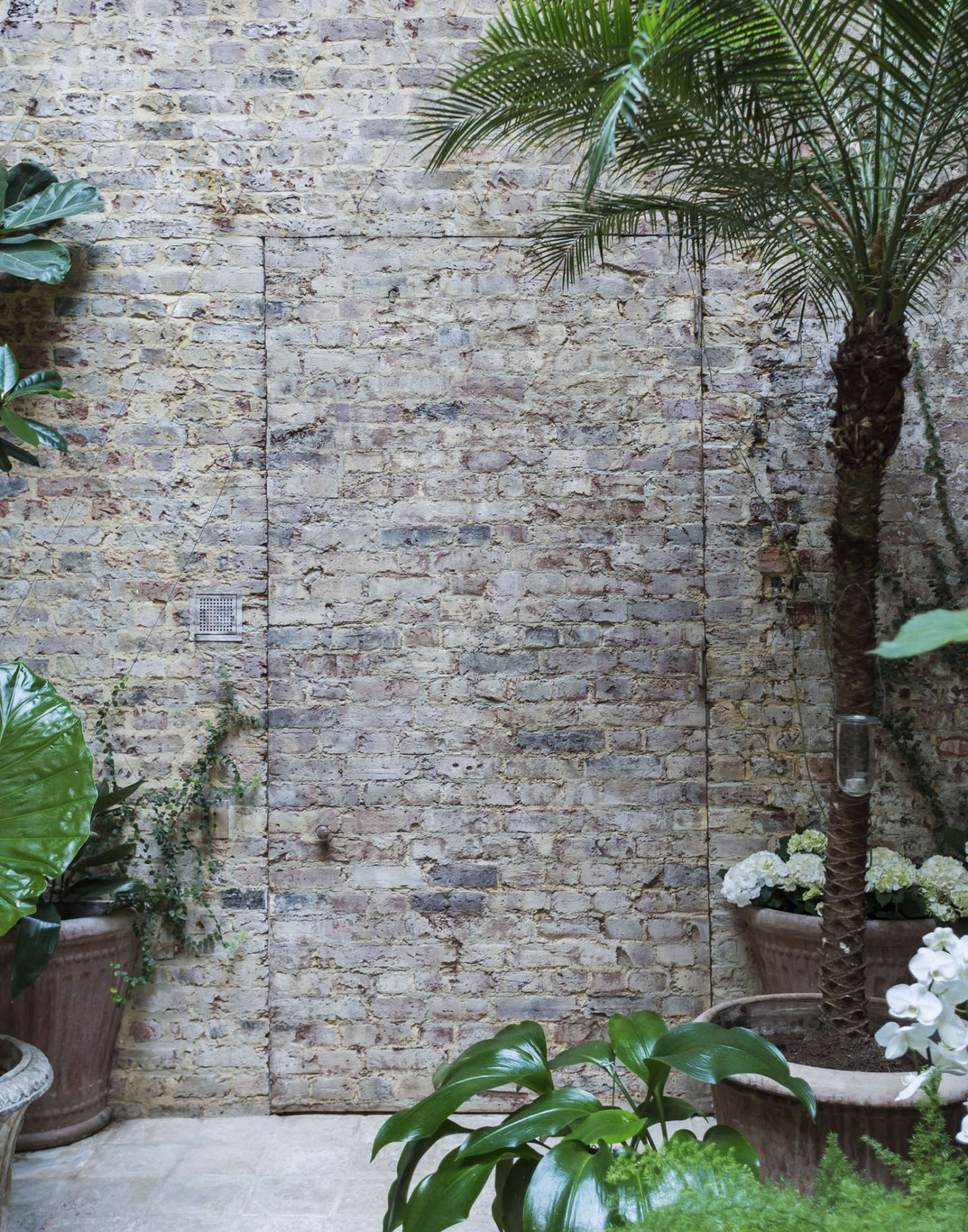 Layers of plaster were stripped from the walls, revealing bare brick Uniacke elected to leave raw. To camouflage a door that connectsthe conservatoryto the original owner&#8