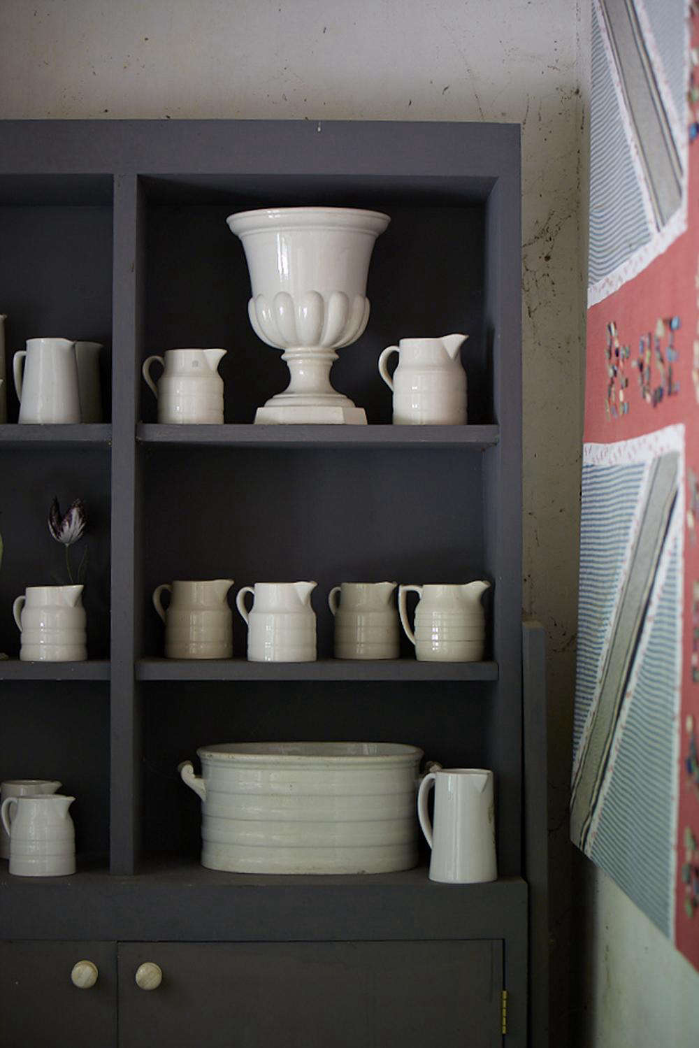 Useful creamware makes a monochrome collection. The vase cupboard is painted the same color as the exterior of the stables.