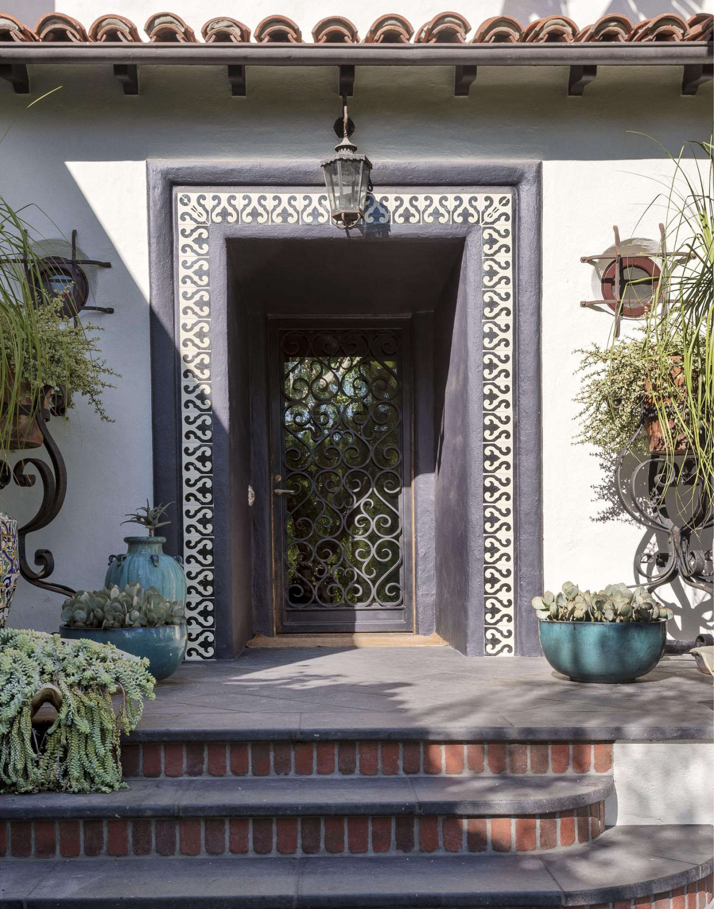 Designers (and siblings) Ramin and Pam Shamshiri added curb appeal to a 1920s Hollywood garden with reclaimed ceramic patterned tile on a stucco facade and redbrick detailing on an entry stairway.