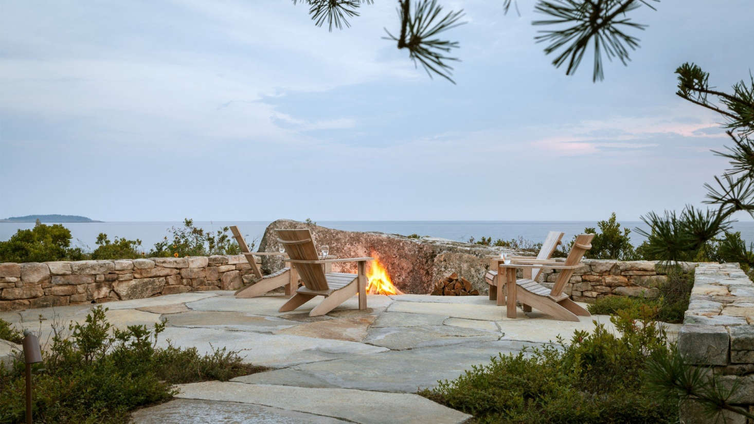 The angled boulder in front of the fire pit is the single largest rock placed on the site. The Adirondack chairs are from Crate & Barrel (though they&#8
