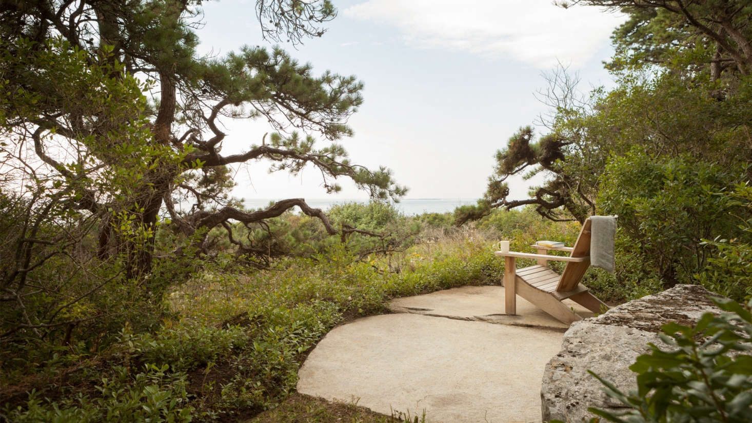 A private seating area on stone slabs is set among an existing grove of pitch pines.