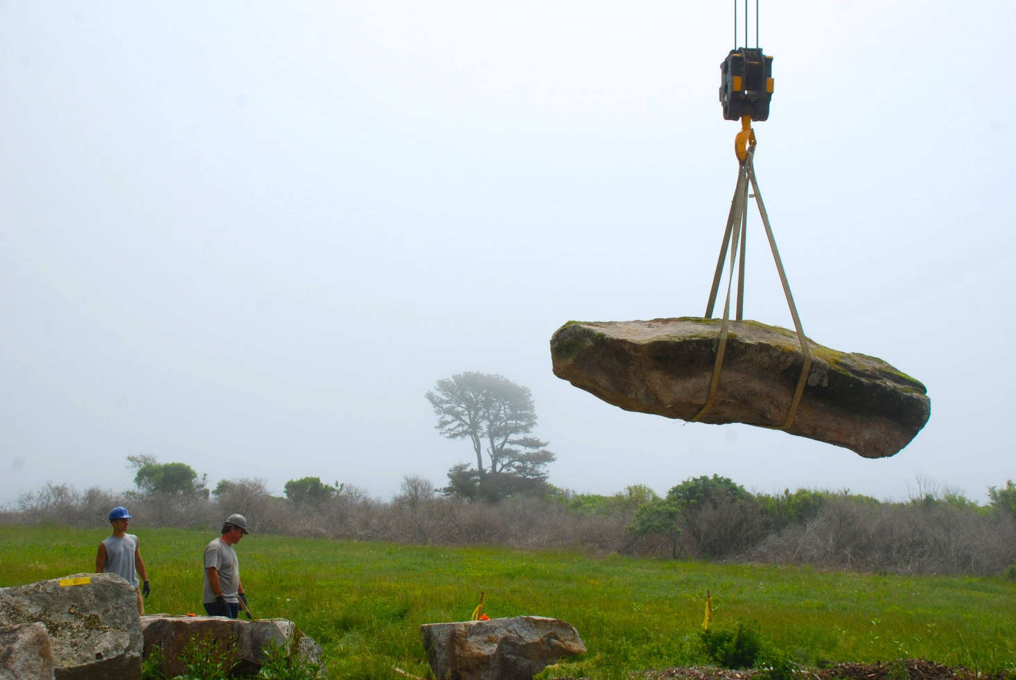 A boulder being laid on the site via crane. Photograph by Todd Richardson.