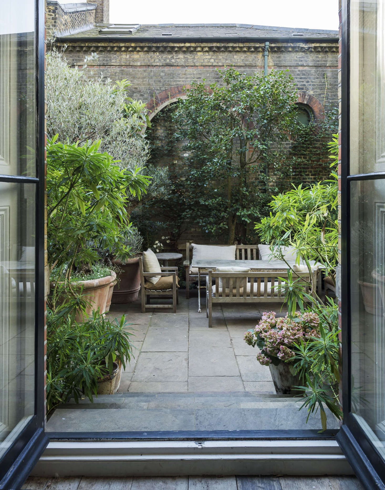 French doors in the living room lead to the walled garden. The terrace is paved with old Yorkstone (a type of sandstone quarried in Yorkshire) and flanking the doorway are two evergreen euphorbia shrubs, which resemble rhododendrons. A newish variety, Euphorbia x pasteuriihas fragrant yellow honey-scented flowers in late spring.