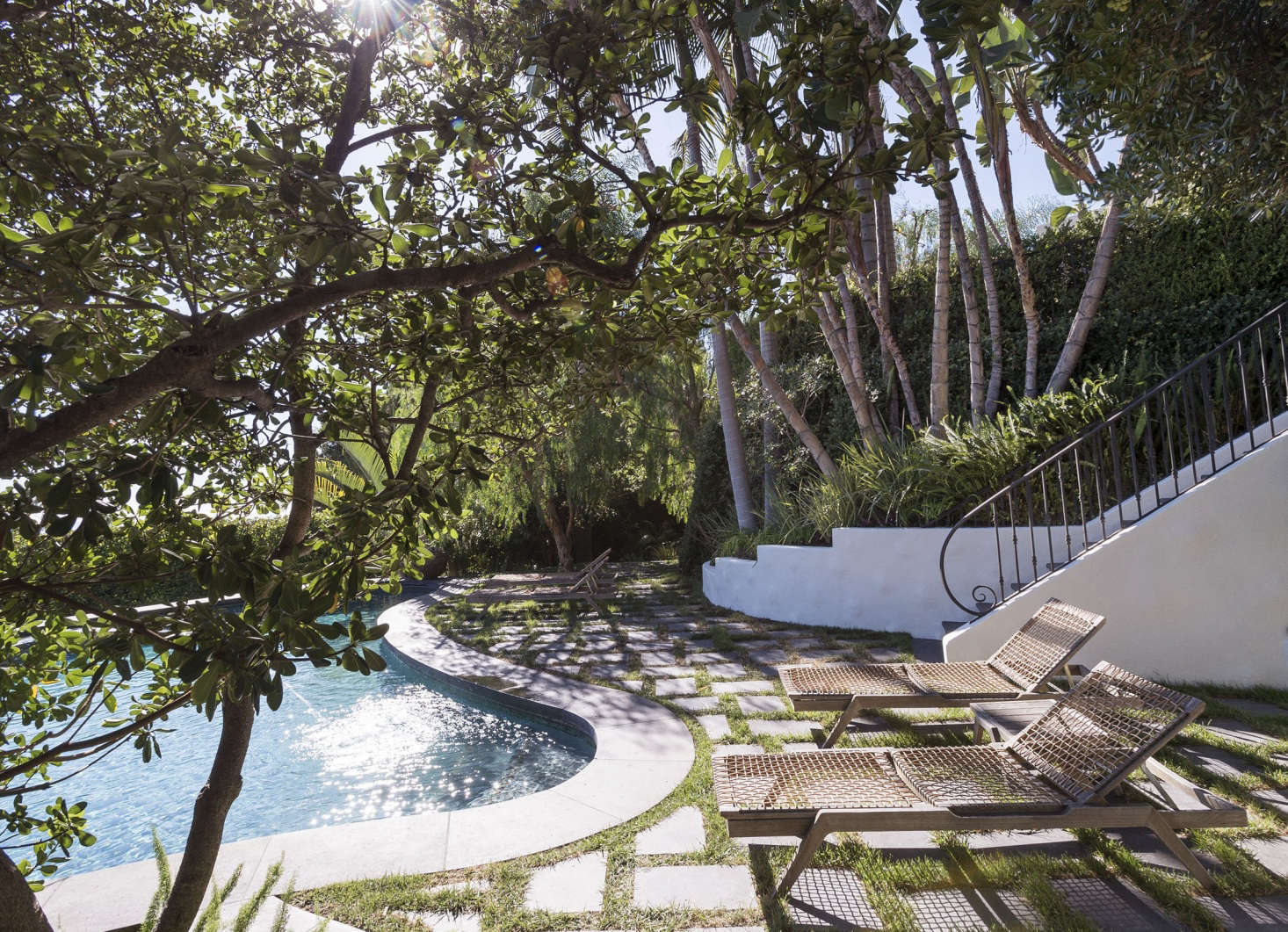 "Black cantera stone pavers are set in a herringbone pattern and ""grouted"" with plugs of turf grass to create a permeable patio to surround a swimming pool in Los Angeles."