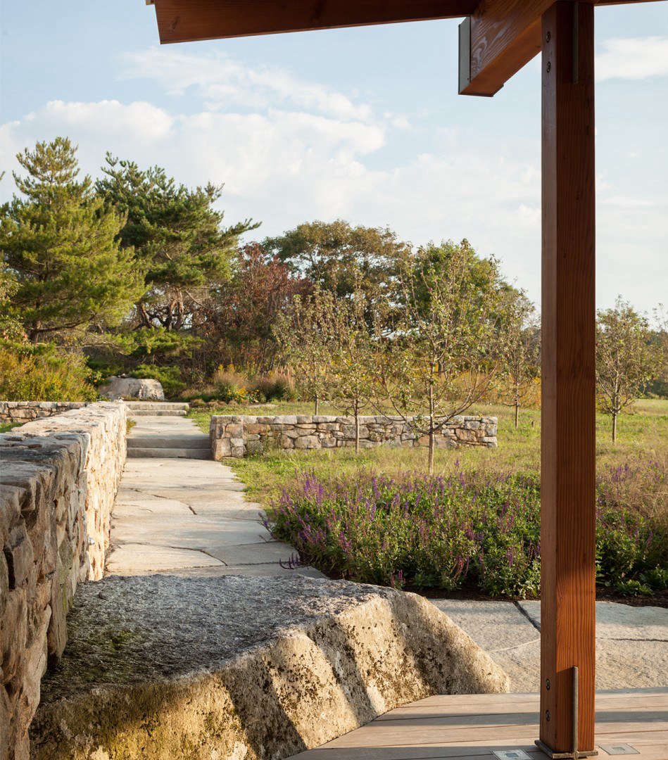 At the entryway, a Rockport granite boulder directs visitors from the parking court toward the front door just off to the right. A small apple orchard flanks the walkway.