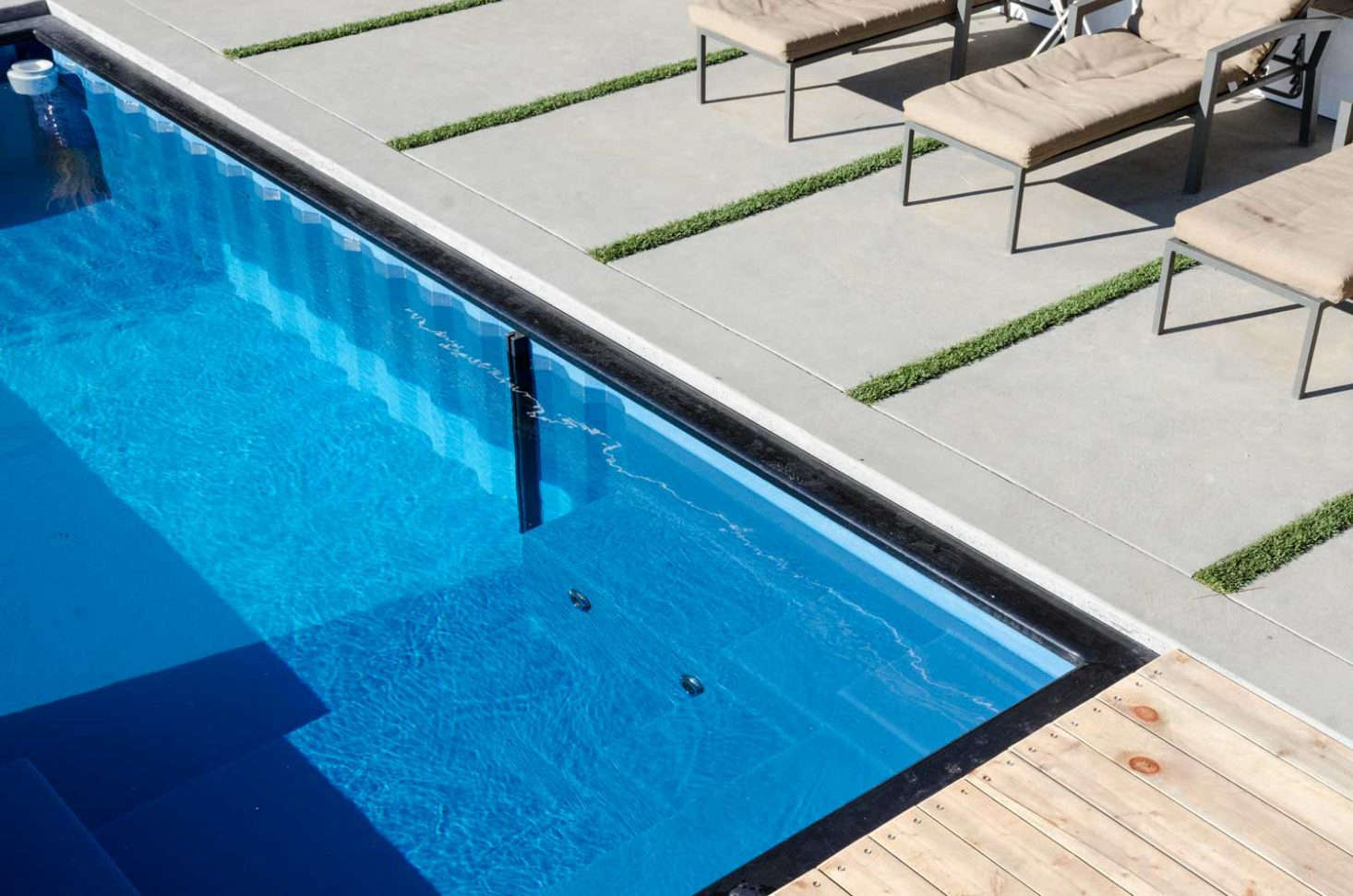 A clear polyethylene wall separates the swimming area from the hot tub portion—which has eight body jets and steps that double as seating.