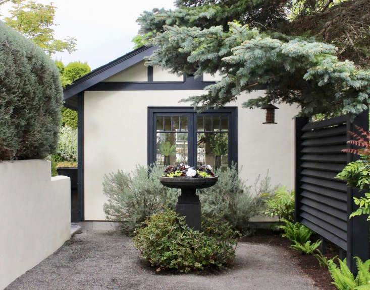 gravel driveway courtyard black fence by Christin geall