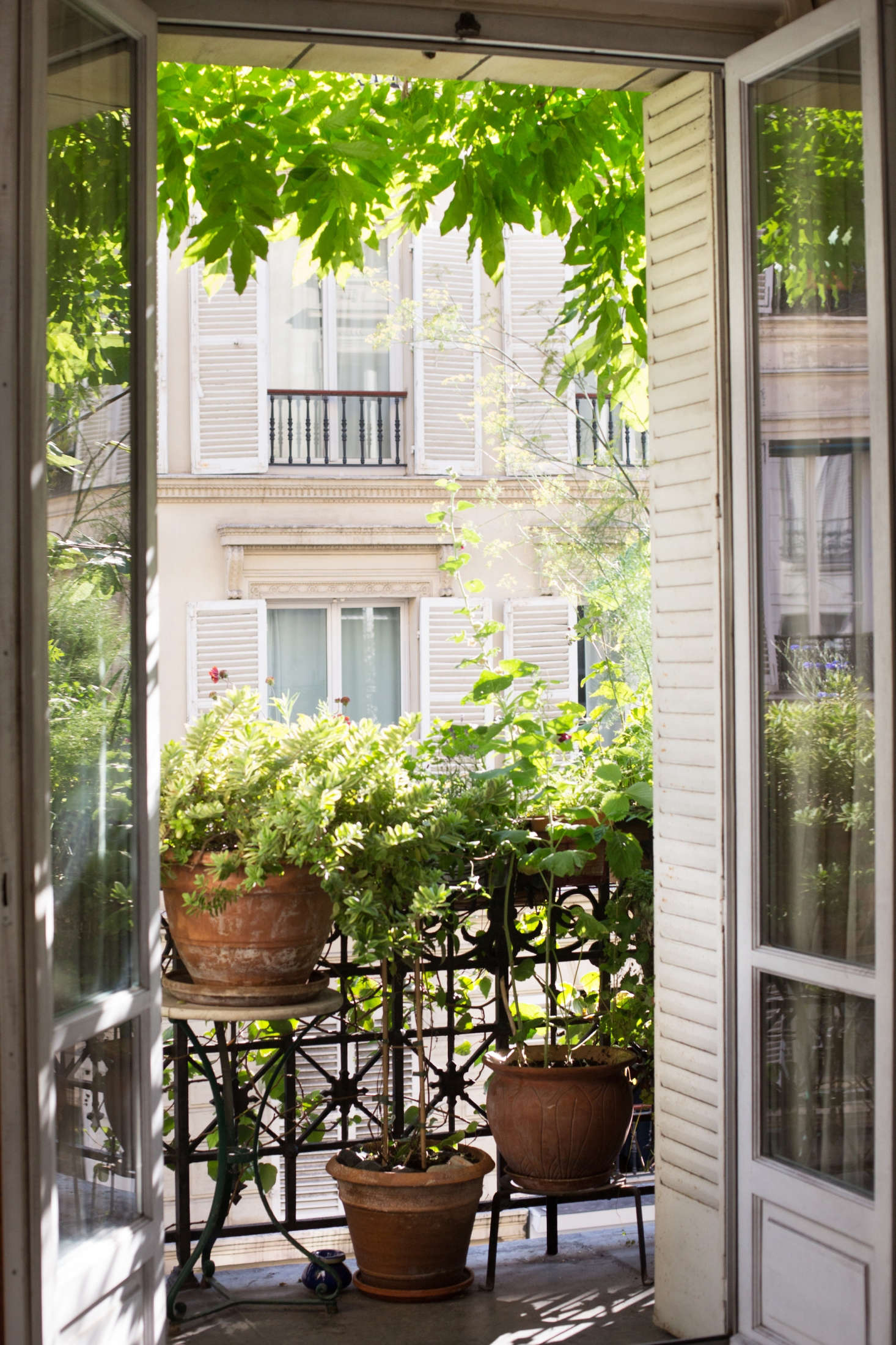 A pair of French doors swing open to connect the flat's living room to the balcony garden.