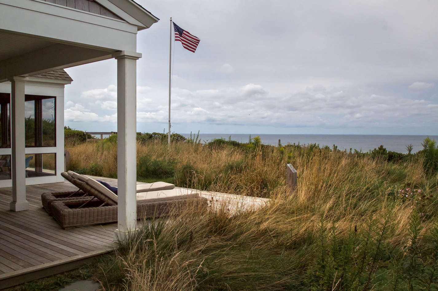 The continuous porches along the bay side are completely engulfed in a sea of grass.