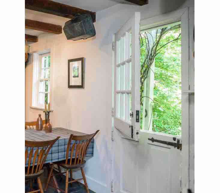 Step inside the Dutch door, into a kitchen with beamed ceilings and a lovely view of the garden.