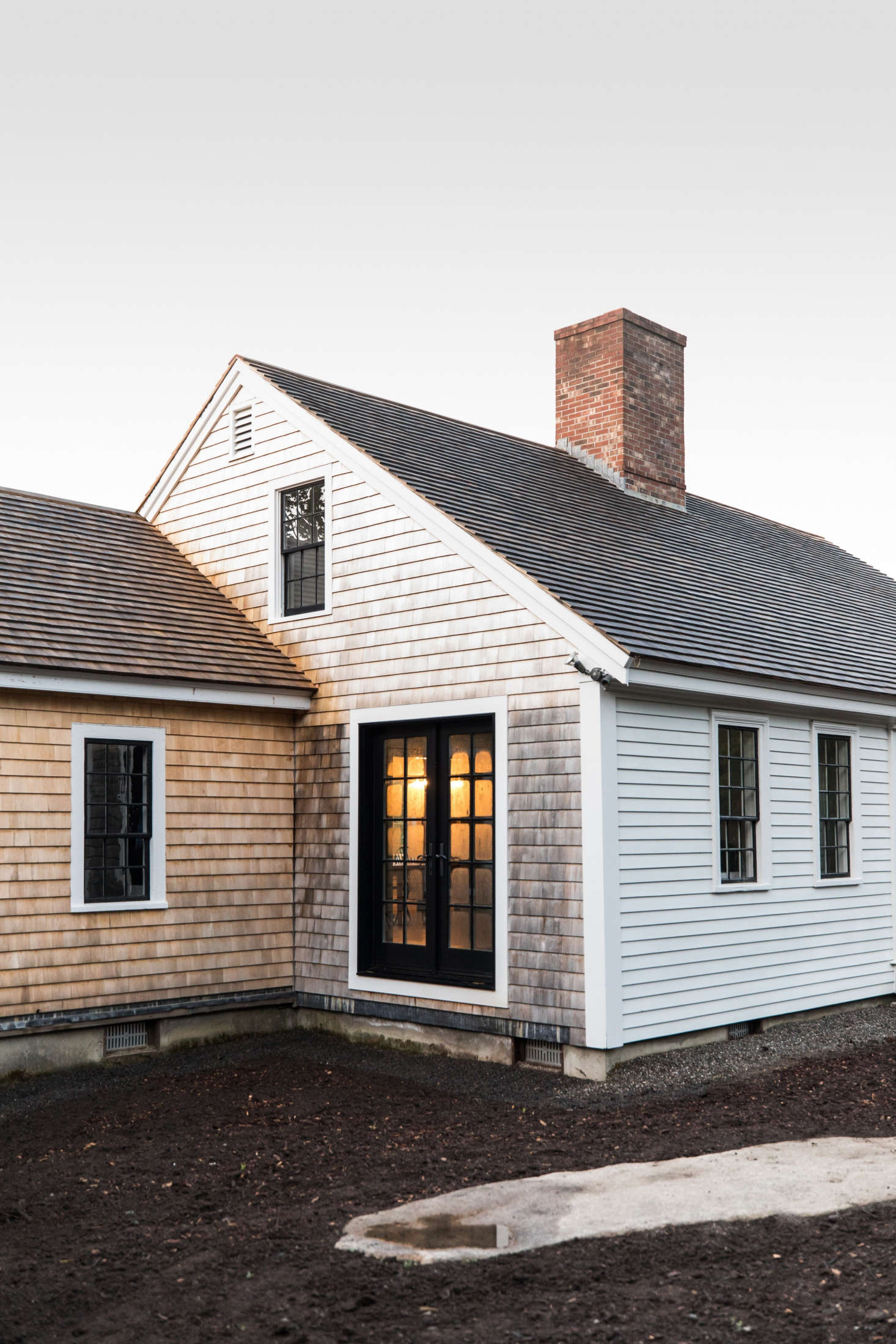 The front of the house is clad in traditional New England clapboards. The sides and small extension on the house are fitted with shingles that will weather. (Esteves is in the process of building a deck in this corner.)