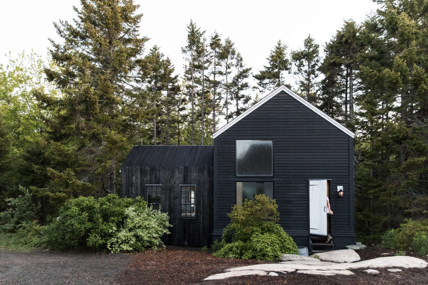 Maine has no shortage of pine trees. The Soot House, pictured here, uses mulch made from the area's fallen spruce trees. Photograph by Greta Rybus, from Curb Appeal: A Classic New England Color Palette on Spruce Head in Maine.