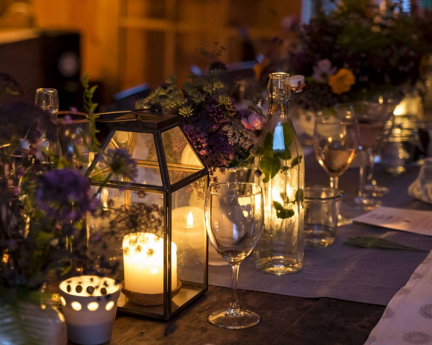 """Presentation is almost everything,"" says Phoebe. ""In addition to dimmed bistro lights overhead, I use softly lit lamps in the corners of the barn, and candle lanterns and votives everywhere. We always have the firepit lit outside."""