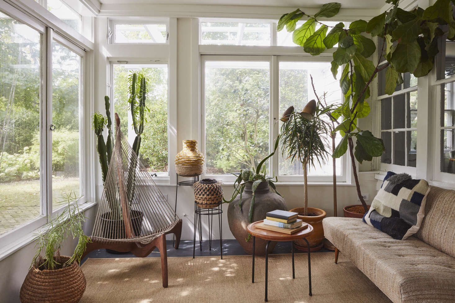 In a sunroom on Long Island, designer C.S. Valentin unified a disparate collection of desert and tropical plants in pots made by his brother, David Haskell of DGH Studio. Photograph by Jonathan Hökklo.