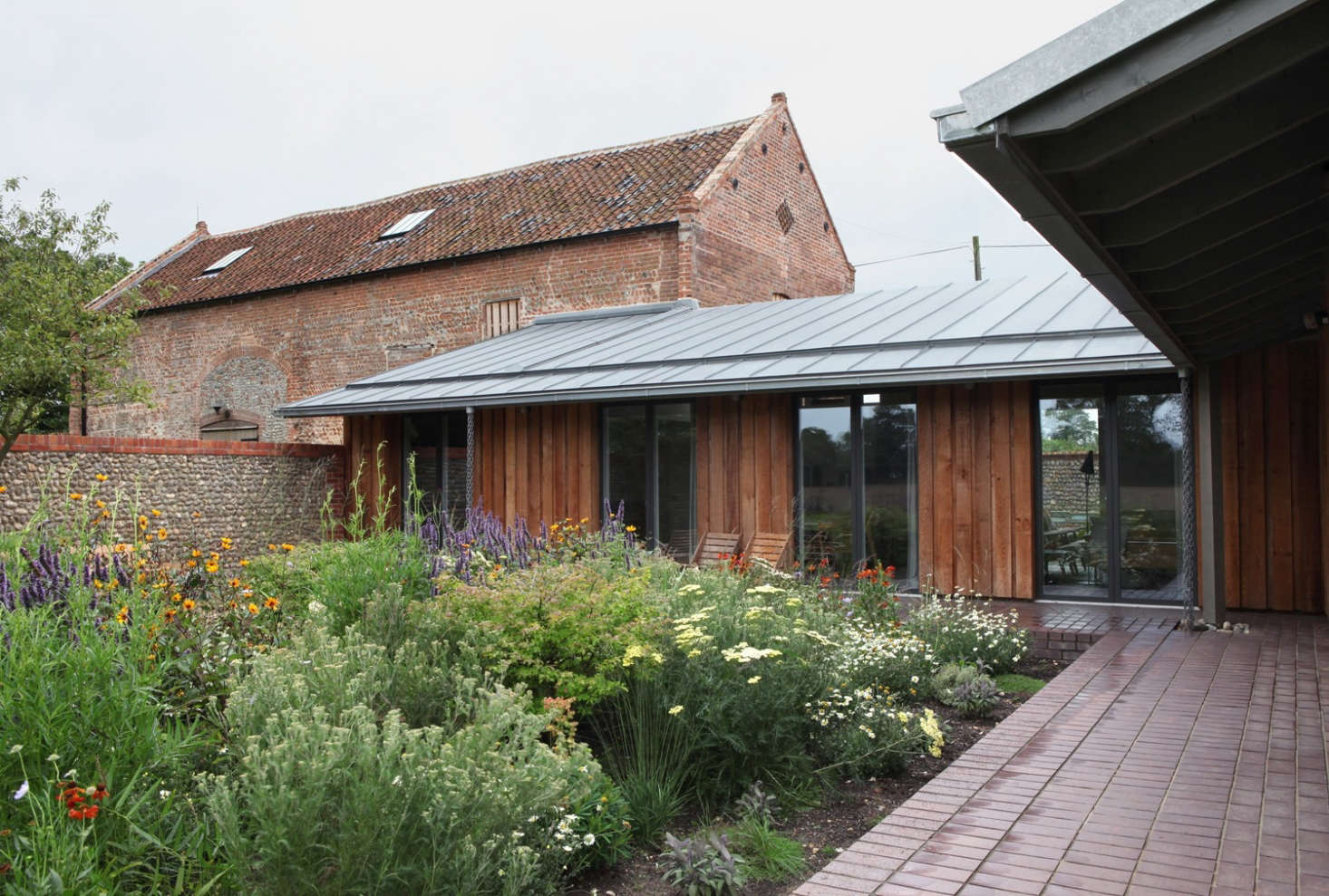 : A view of one of the two inner courtyards, formed by the connection of the tithe barn (L) and the piggery (R). Photograph by Ioana Marinescu. See more in A Rural Remodel in Norfolk, Tithe Barn and Piggery Included.