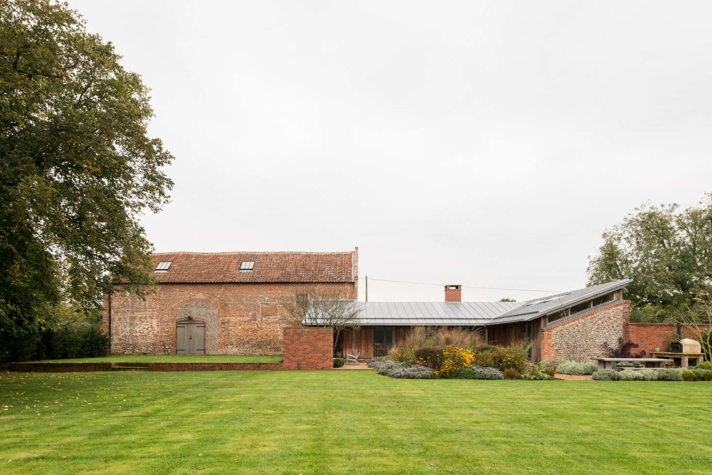 The building on the left is anold tithe barn, where in centuries past the local clergy stored the taxes they collected from surrounding villages. At right is the remodeled piggery, in which Erlam and her husband and two children live.
