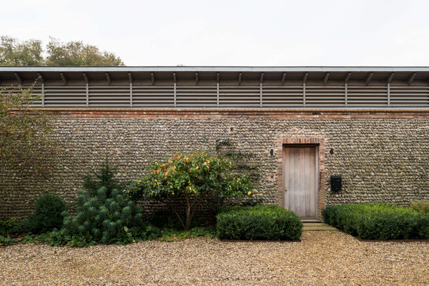 Against the flint facade of the piggery, Erlam planted a mix of shrubs and perennials such as euphorbia (at Left), edged by a gravel courtyard.