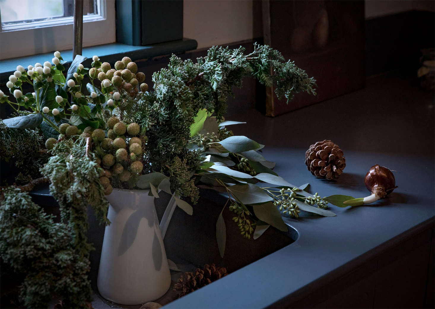 A quick trip outdoors provided the base for a still life with holiday boughs, with foraged juniper evergreens. At the grocery store, I found seeded eucalyptus as well as white Hypericum berries. For a bit of the exotic, I choose Brasilia from my local florist.