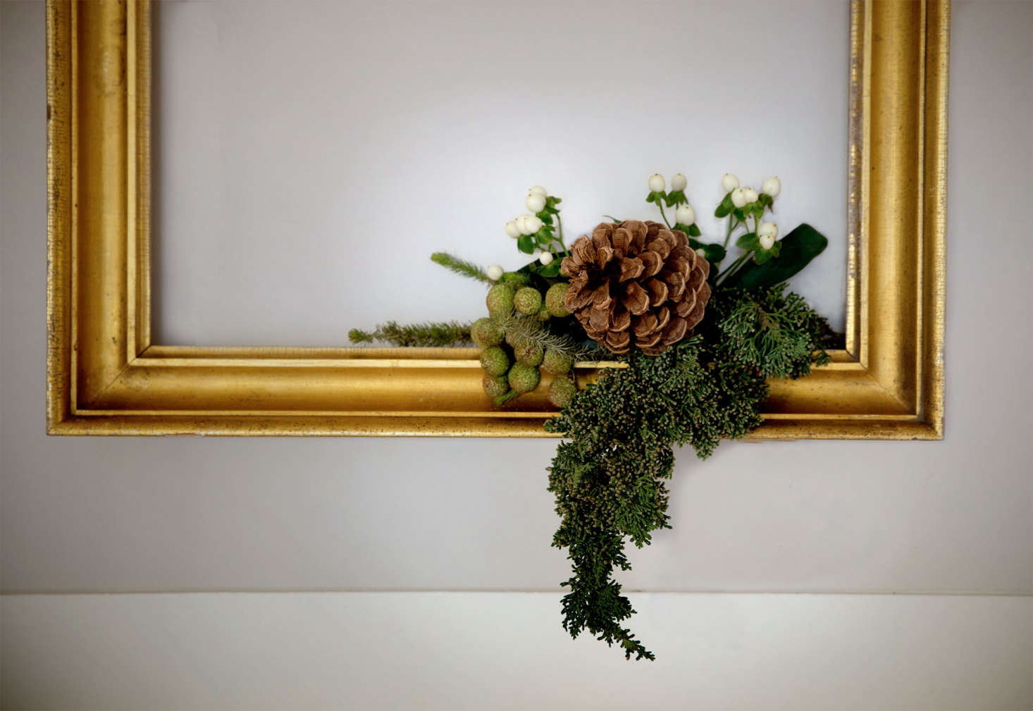 I started with a large branch of juniper, which I simply stuck into the frame. From there I began to build, adding a pine cone and berries until I had the basis of the composition.