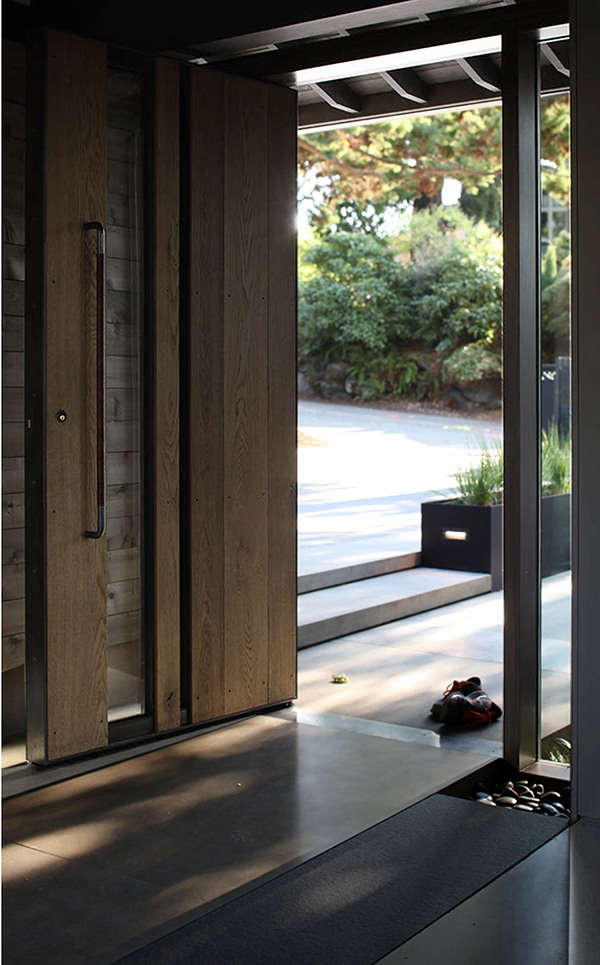 The new front door is a custom design, made of heat-treated oak planks in a pivoting steel frame. The heat treatment, explains architect Steve Mongillo, makes the wood more resistant to moisture and decay.