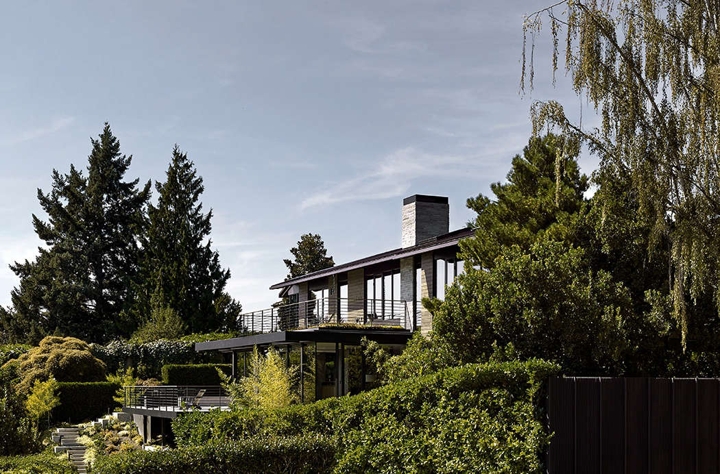 The back of the house looks toward Seattle's Lake Washington. Though the house's footprint remained unchanged, the architects flattened a formerly vaulted dining room ceiling to allow for a new, top-floor deck off the master bedroom. From a lower deck located off the kitchen, poured concrete stairs wind down to another patio and lawn.