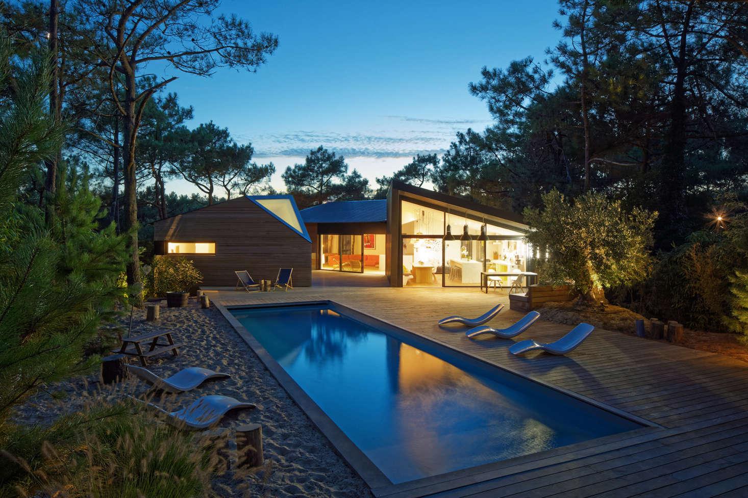 在晚上,一个客厅,把阳台和屋顶的灯光照亮。