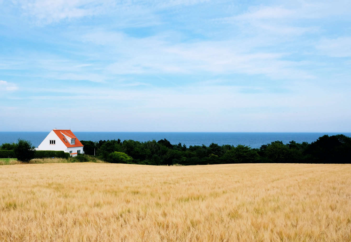A red roof adds color to a landscape in Tejn on the northeastern coast of the island of Bornholm. Photograph by Lars Plougmann via Flickr.