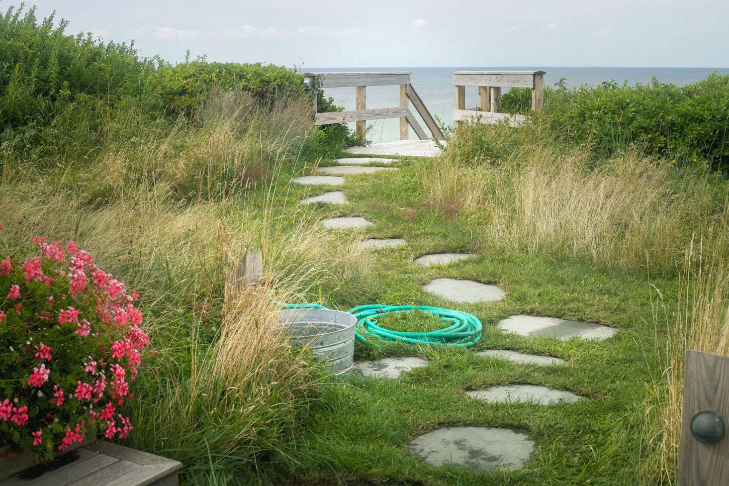 At Merryfield Cottage in Truro, Massachusetts, owners Steve Corkin and Dan Maddalena installed a convenient rinsing station, including hose and water-filled bucket, beside the beach path. See Tales from Truro: An Untamed Landscape Channels Thoreau's Cape Cod.