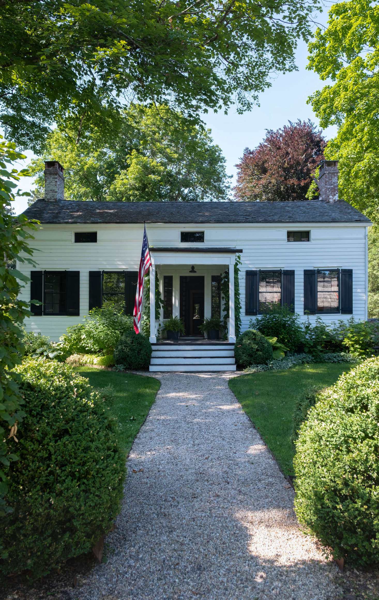 The circa-1830 house is set back from a main street in Claverack, where tall hedgerows abut the road and conceal the historic houses and sprawling gardens behind.