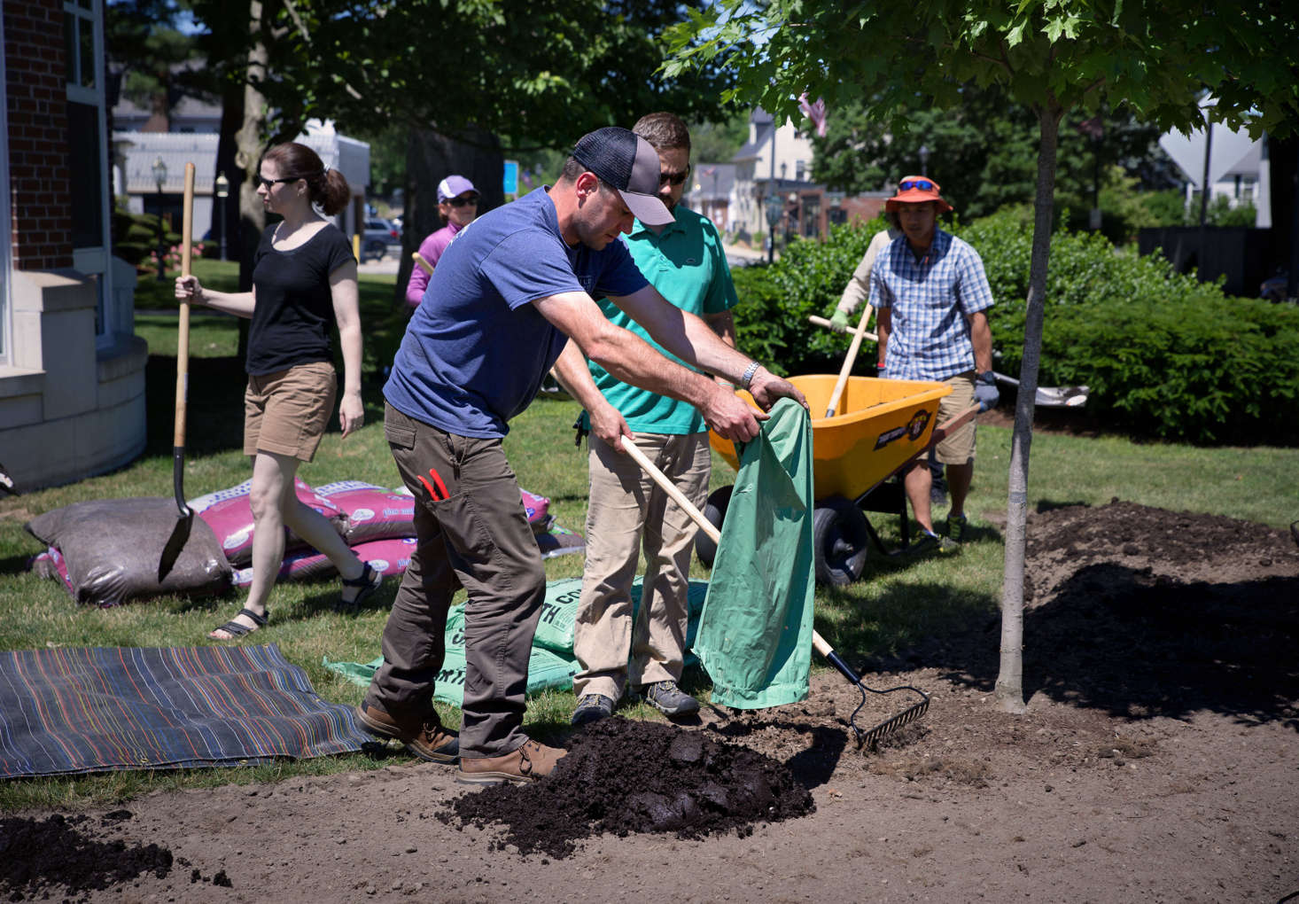With the help of his class, Mark Richardson adds local, organic compost to the site. The New England Wild Flower Society uses only compost and organic mulch to enrich its soil, never fertilizers.