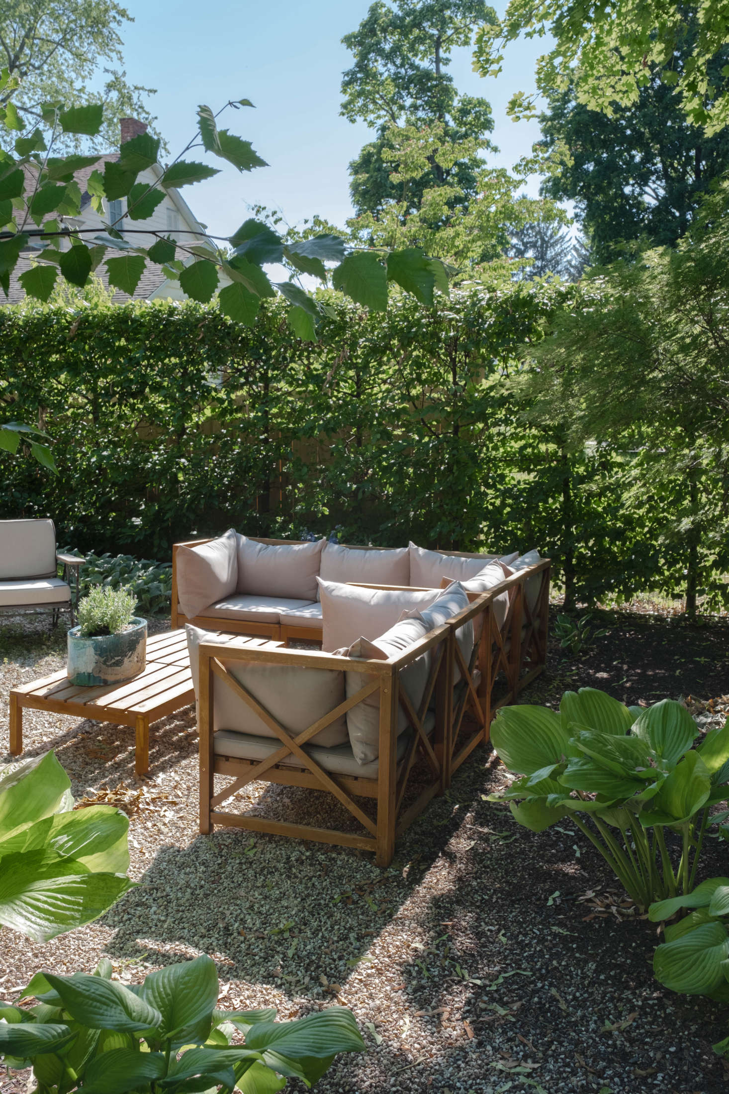 A summer living room, set for lounging. The outdoor furniture was all in place when the couple moved in.