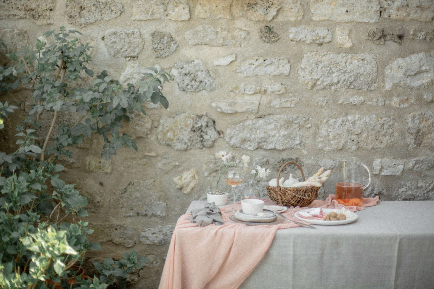 An undone-chic table at the French country house, set with summer drinks, freshly picked white asparagus, and a simple white floral arrangement.