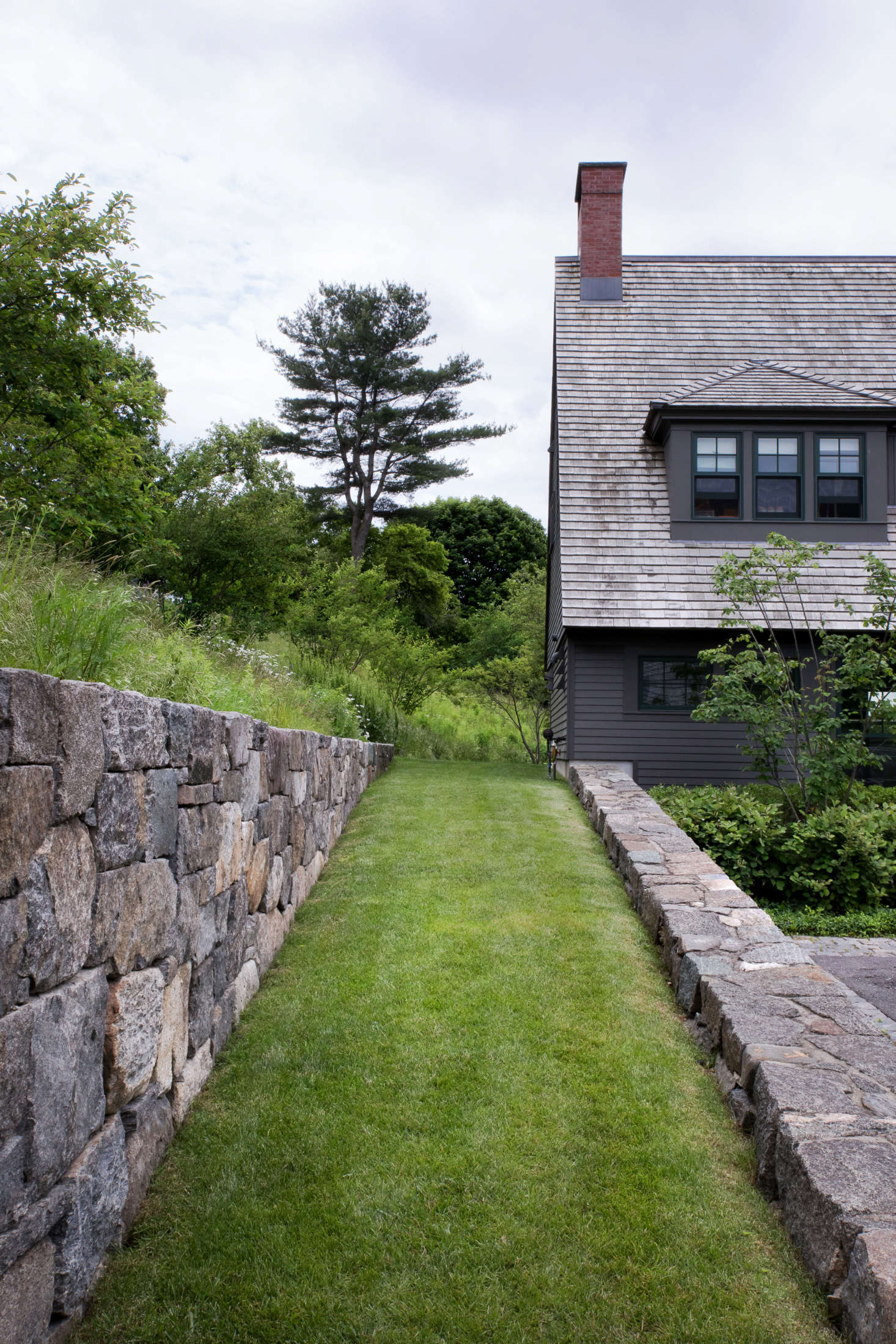 A lawn ramp, built with the type of large fieldstones typically used in farms, connects the entry level of the house to the upper outdoor living areas, where another retaining wall frames views of working farm fields. Mature trees were preserved whenever possible to help site the new construction and landscape within its setting. Visible in the distance is one of the largest pines found on the property, which was preserved and pruned.