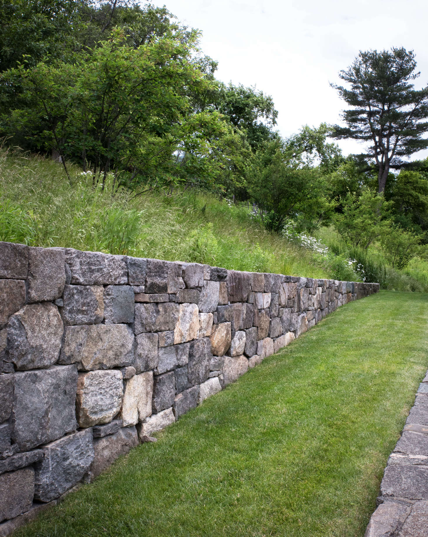 "The four, new, fieldstone walls on the property were constructed using locally sourced stones carefully chosen for its character and appearance. All new walls utilized stones that were intentionally larger and rough-hewn to blend with the rustic surroundings. Some show a combination of ""faces,"" some are naturally weathered, while others show a tooled edge; all so that the newly built wall feels older."