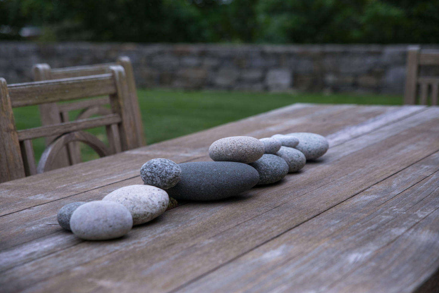 The outdoor dining table features a somewhat more loosely constructed stone wall of its own.