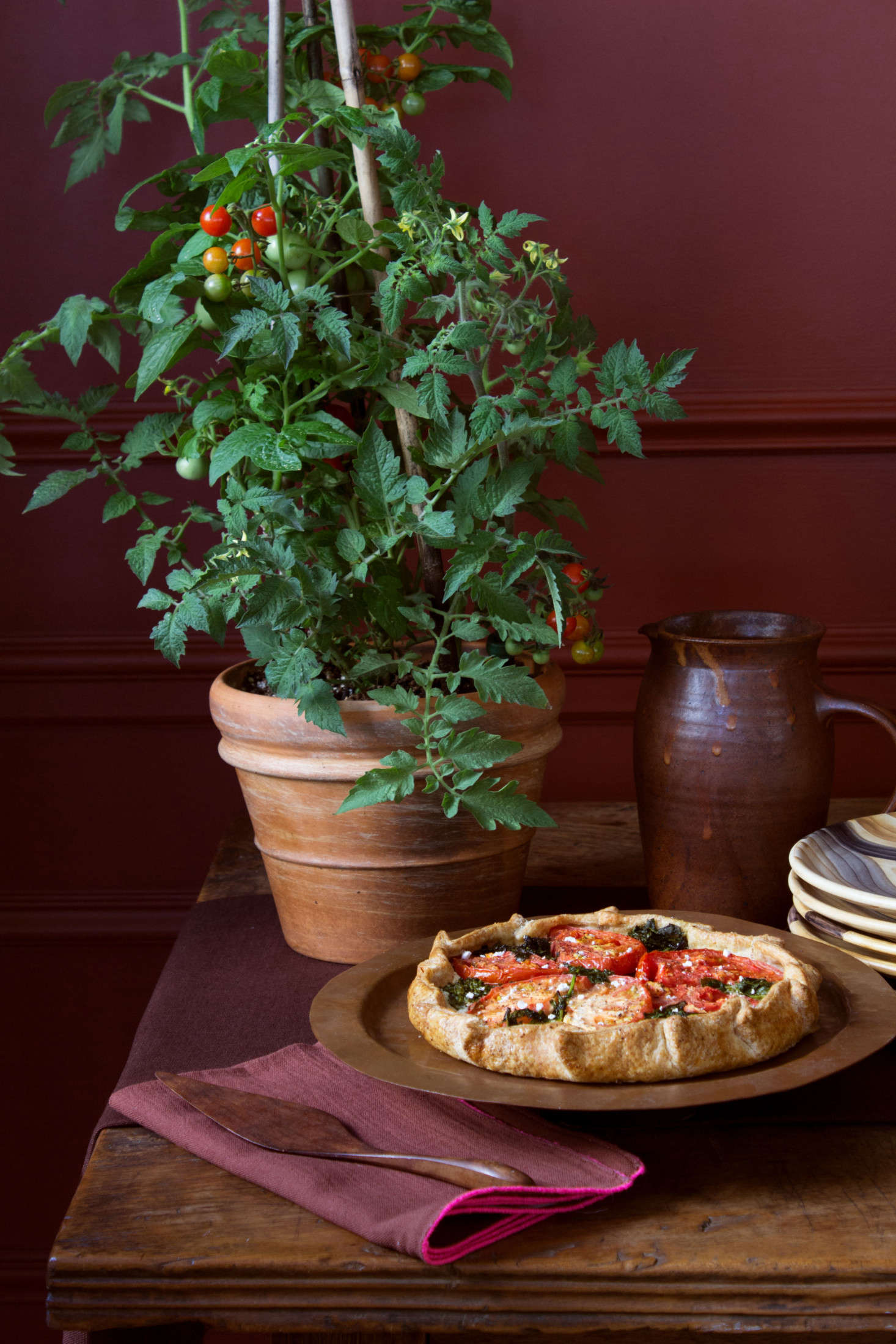 """Just repurpose a plant from your patio garden as decor,"" recommends Stark. On the menu is a tomato galette from Colson Patisserie in Brooklyn.  And for a fitting tomato-red backdrop, the walls are painted in Benjamin Moore's Red Rock."
