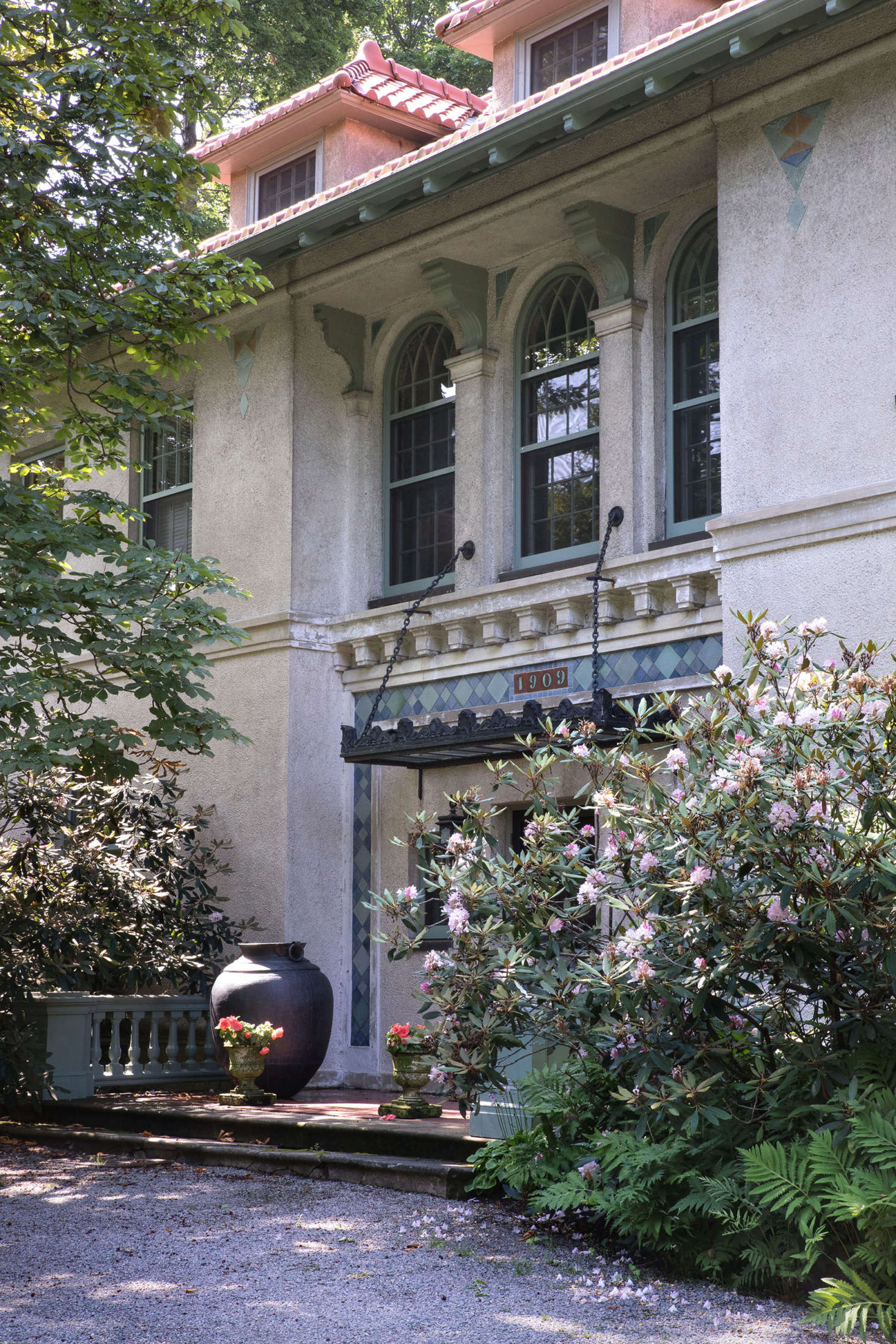 Flanked by ferns and mature rhododendrons, the front entrance of the house maintains a stately appearance.