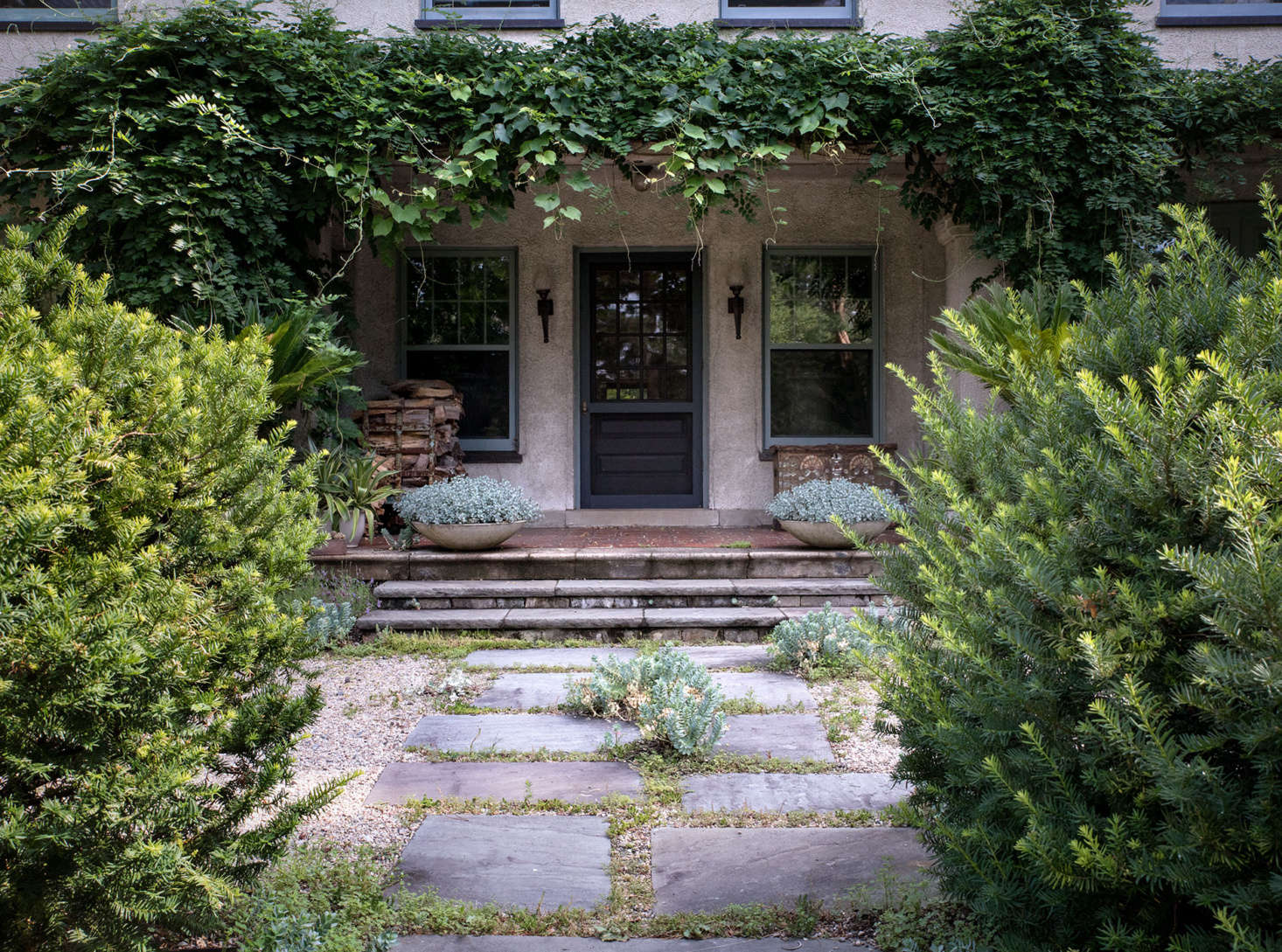 Framing a hand-hewn stone path, loosely shorn yews, as well as untamed vines and self-sewn plantings, conjure an atmosphere of old-world charm.